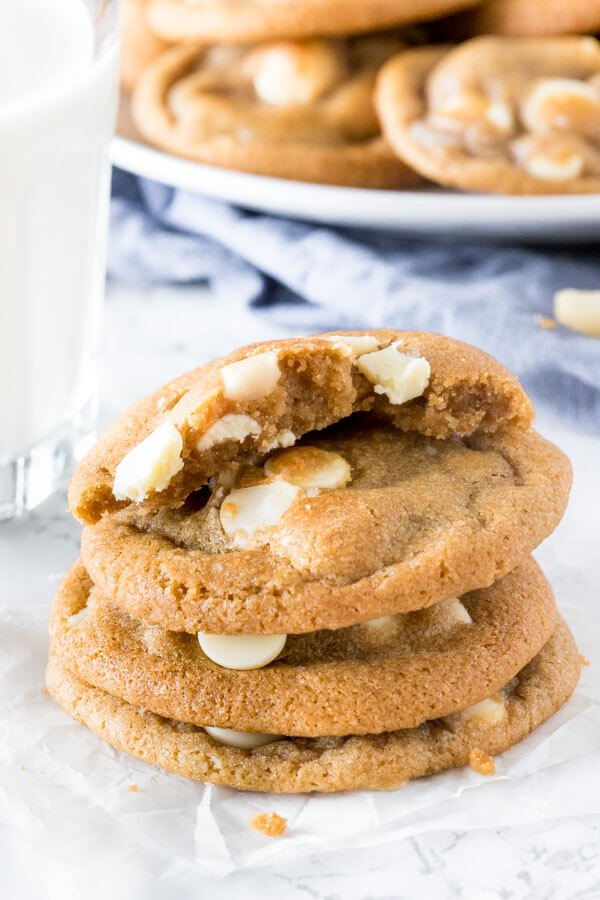 A stack of subway copycat white chocolate macadamia cookies with the top cookie broken in half to show the chewy center.