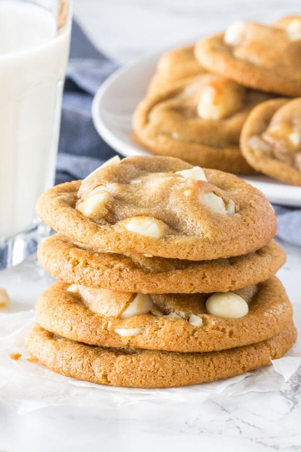 A stack of soft, chewy white chocolate macadamia cookies with golden edges. With a glass of milk and extra plate of cookies in the background.