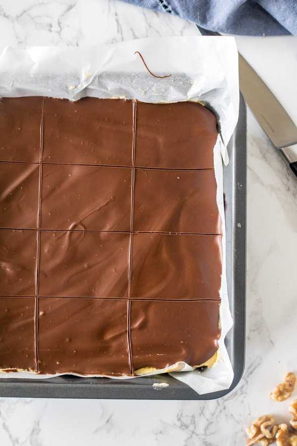 A pan of classic Nanaimo bars after they're almost done hardening and the chocolate on top has been scored.