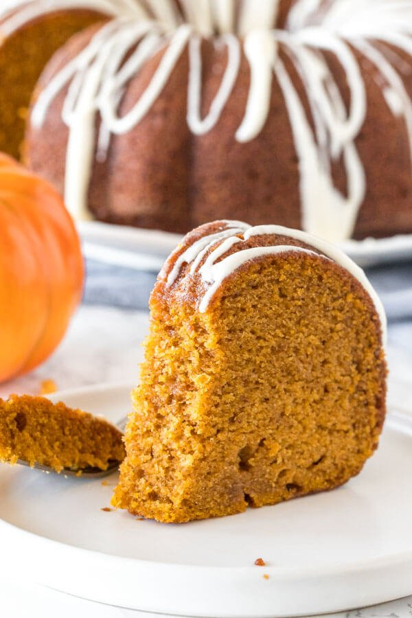 A slice of pumpkin spice bundt cake with cream cheese icing with a bite taken out to show the moist cake texture.