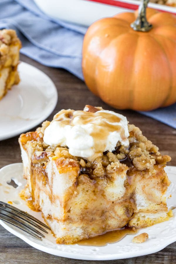 A slice of pumpkin French toast casserole with streusel topping with whipped cream and maple syrup to serve
