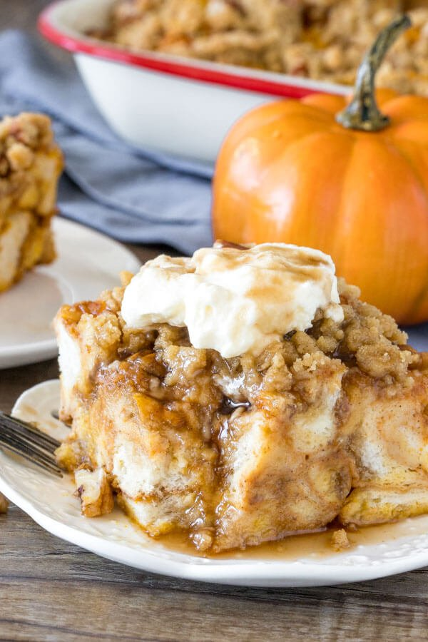 A slice of pumpkin french toast bake with a bite taken out of it as whipped cream and maple syrup drizzle down the sides.