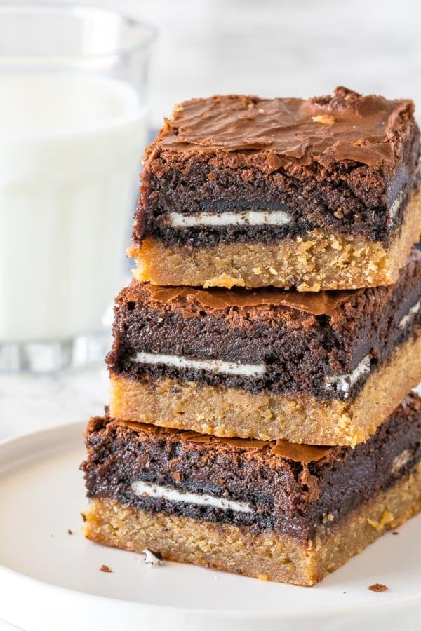 A stack of 3 peanut butter slutty brownies taken from the side to show the peanut butter cookie bottom, Oreo middle and brownie top layer.