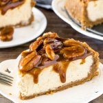 Slice of pecan pie cheesecake with gooey topping.