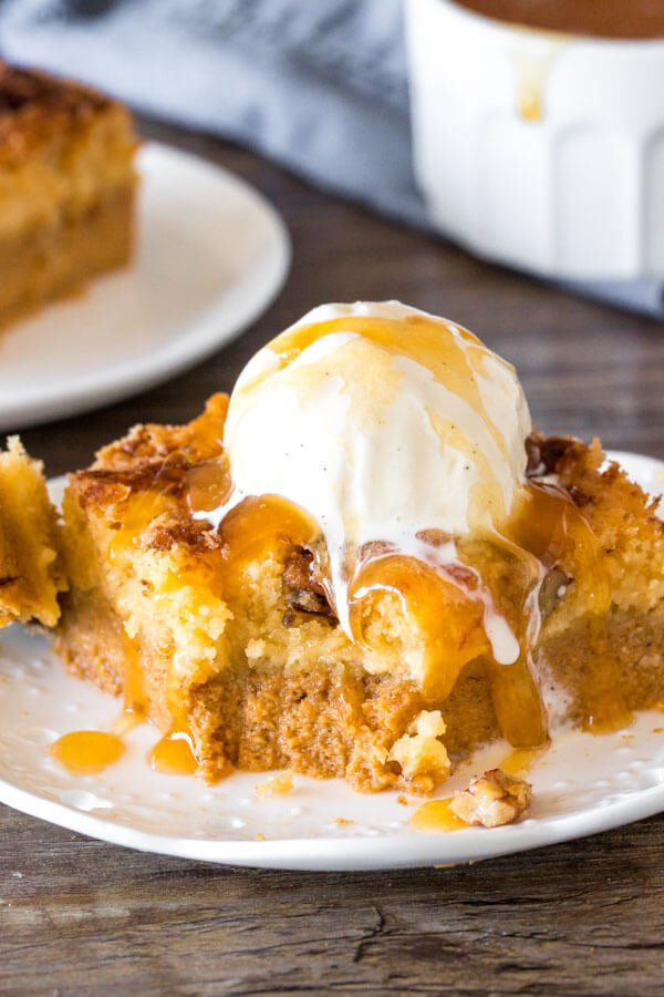 A slice of pumpkin dump cake showing the pumpkin pudding bottom and gooey butter cake topping served with ice cream.