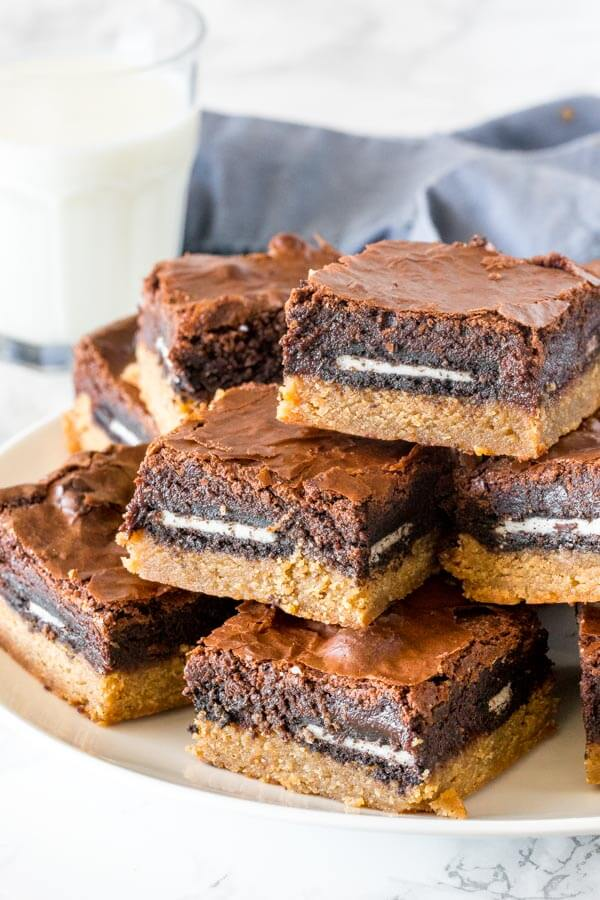 A plate of slutty brownies with a chewy peanut butter cookie bottom.