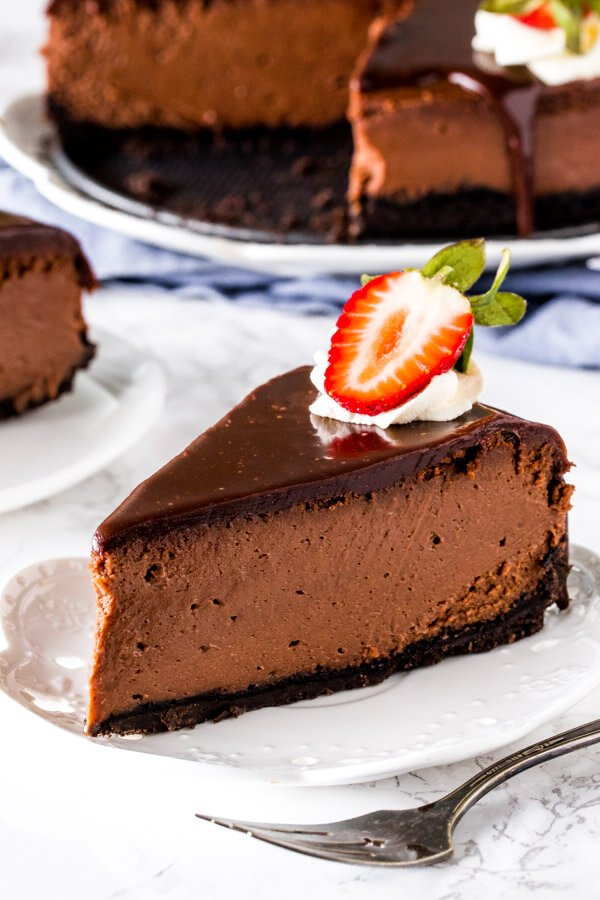 A slice of creamy Nutella cheesecake with an Oreo crust and Nutella ganache on top.