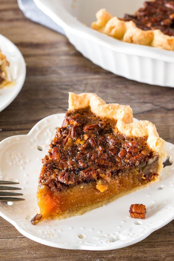 A slice of pecan pie with fluted edges on a white plate with the rest of the pie in the background.