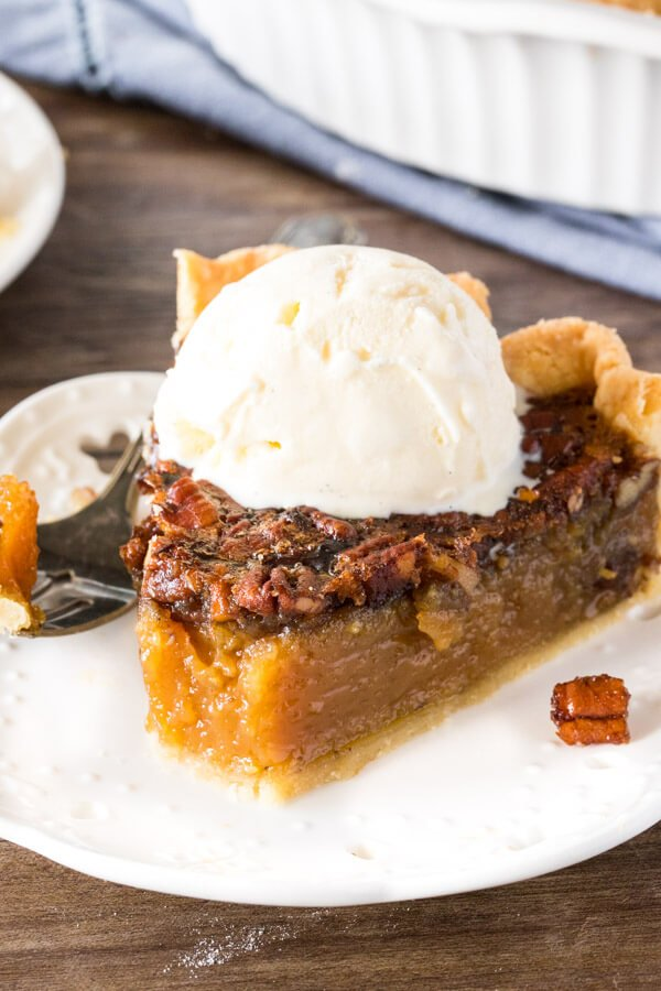 A slice of pecan pie with a scoop of ice cream on top and a bite taken out to show the chewy texture.