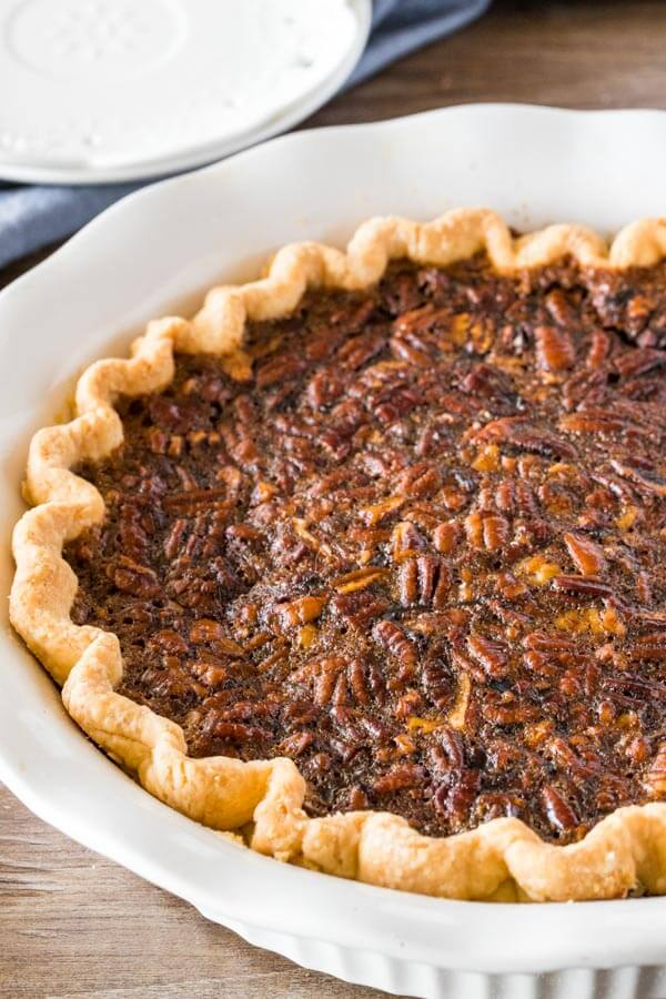 Baked pecan pie in a white pie dish fresh from the oven.