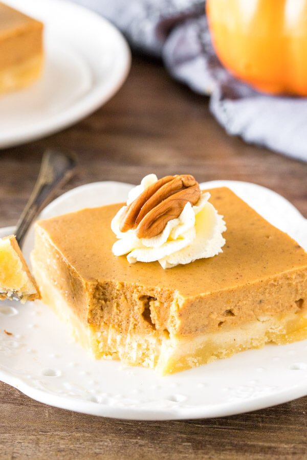 A slice of pumpkin pie bars with a bite taken out to show the creamy texture.