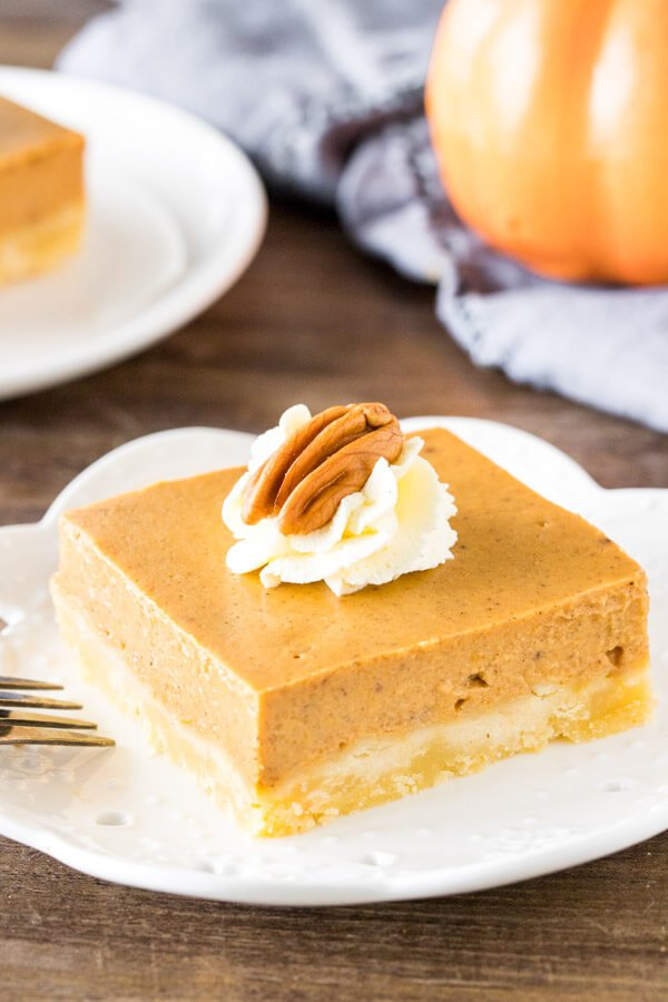 A slice of pumpkin pie bars with easy shortbread crust and whipped cream on top.