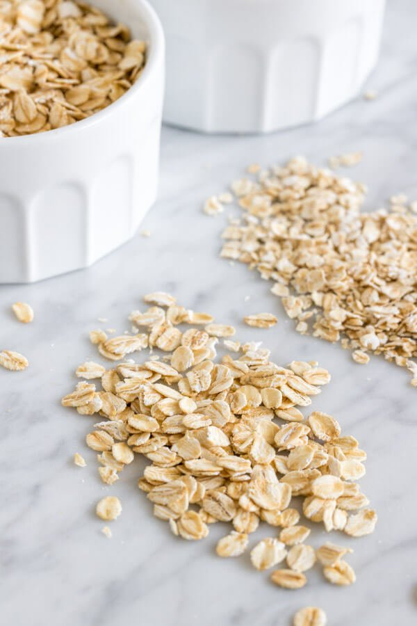 Close up rolled oats beside quick oats on a marble surface