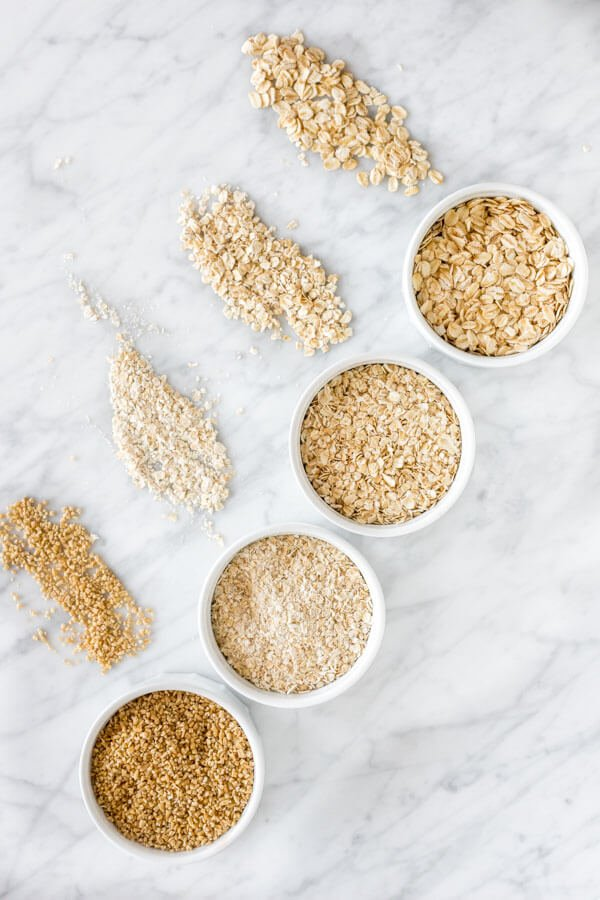 Old-fashioned oats, quick, oats, instant oats and steel cut oats displayed top to bottom on a marble surface.
