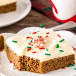 A gingerbread cookie bars with cream cheese frosting with a bite taken out to show the soft, chewy texture.