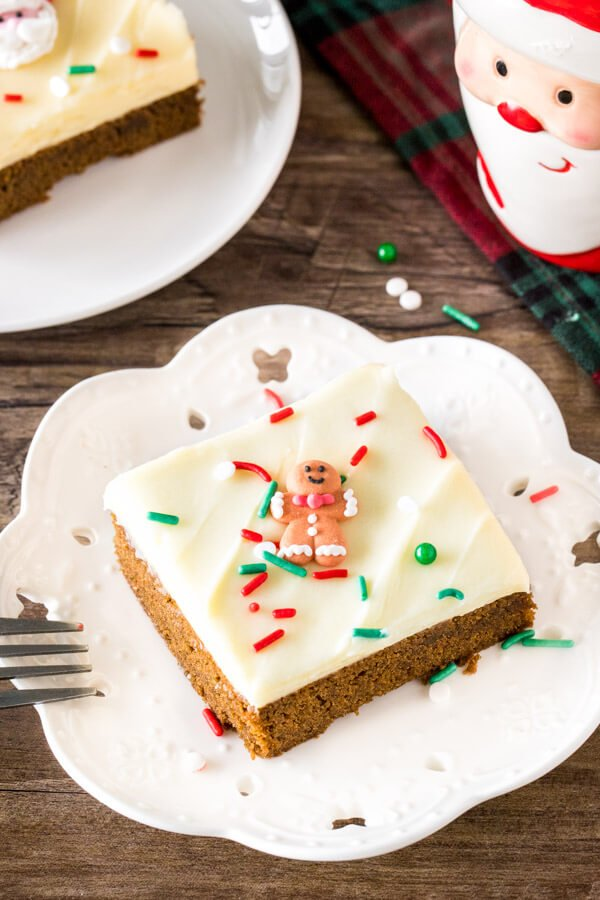A slice of gingerbread cookie bars on a white plate topped with frosting and sprinkles