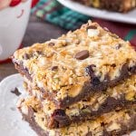 A stack of 3 christmas magic cookie bars with a gingersnap crust and coconut topping.