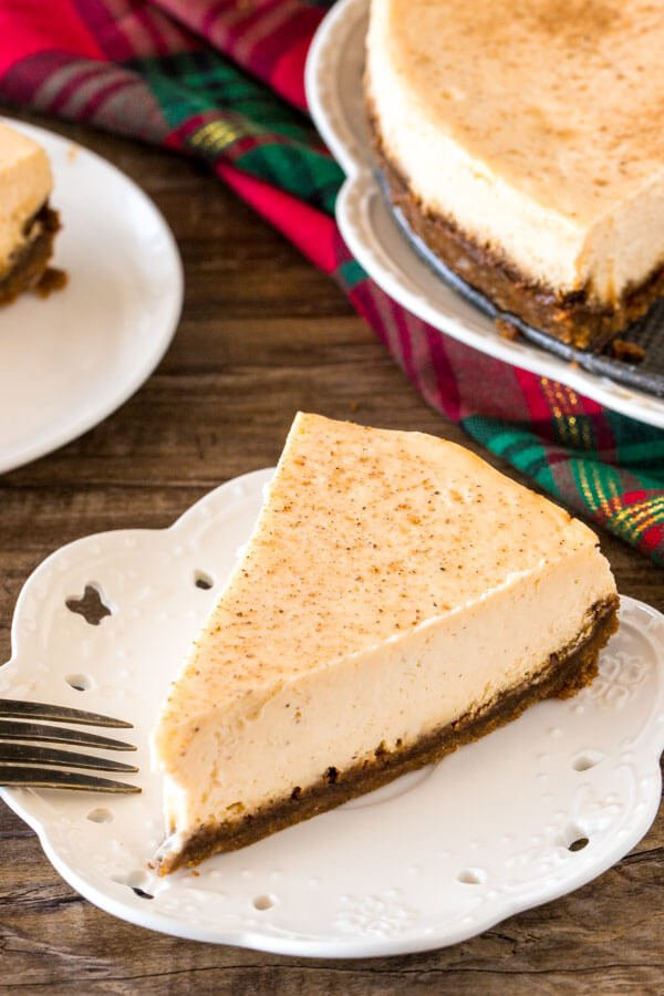 A slice of eggnog cheesecake on a white plate.