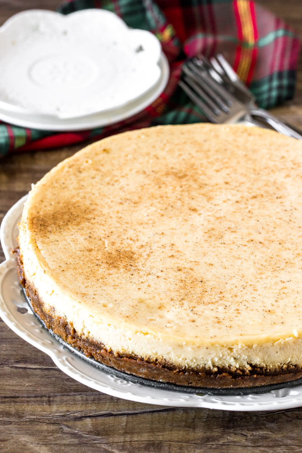 An entire eggnog cheesecake sprinkled with nutmeg on a white plate.