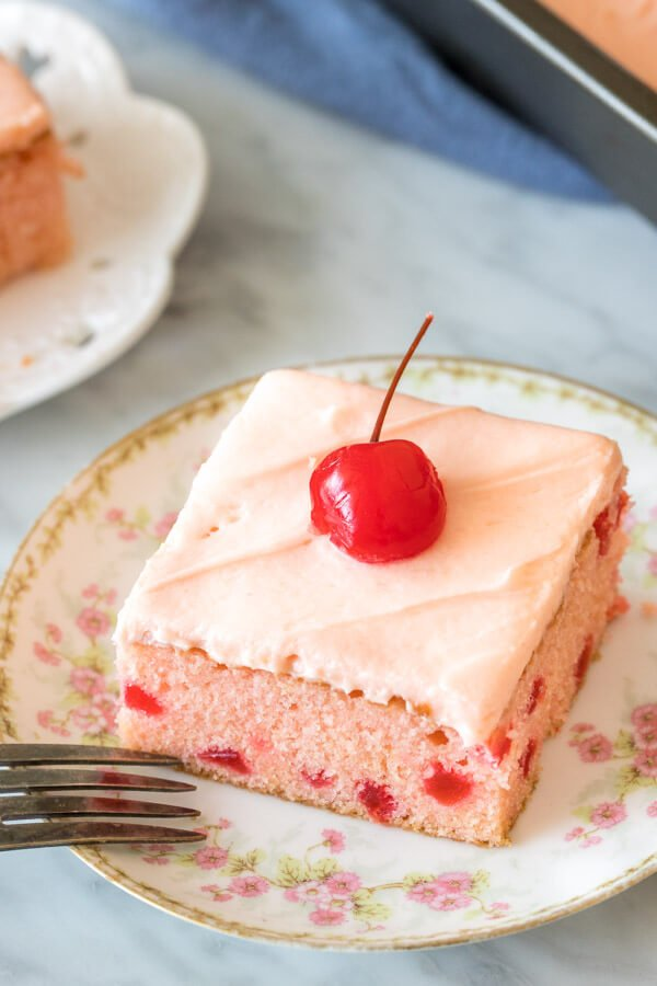 Slice of cherry cake with cherry frosting and a cherry on top.