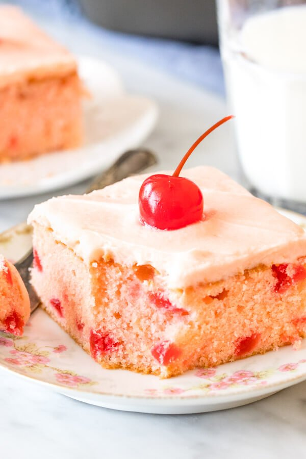 A slice of cherry chip cake with a bite taken out of it.