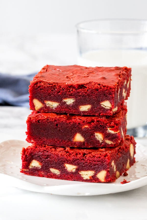 A stack of 3 red velvet white chocolate chip brownies.