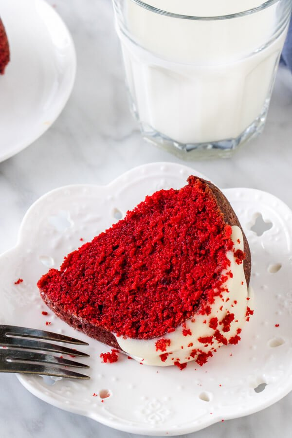 Slice of red velvet cake on its side with a glass of milk.