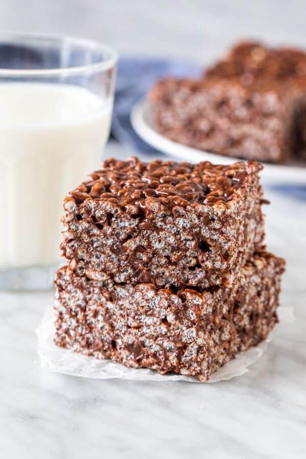 2 chocolate rice krispie treats stacked with a glass of milk.