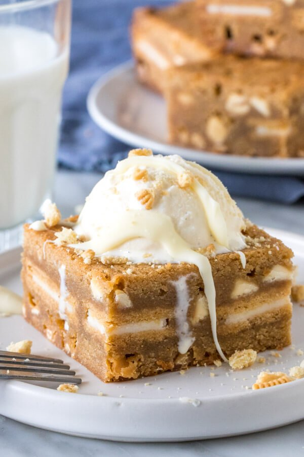Golden oreo white chocolate chip blondie with a scoop of ice cream on top.
