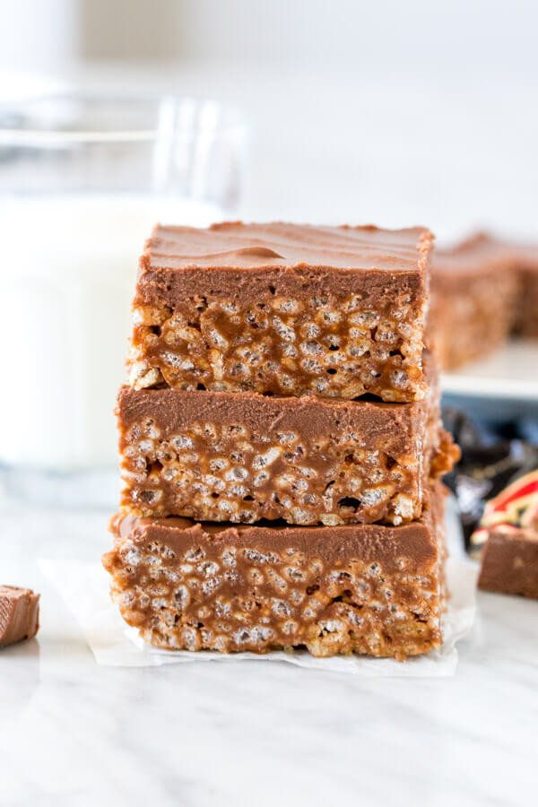 Stack of 3 mars bar squares with glass of milk.