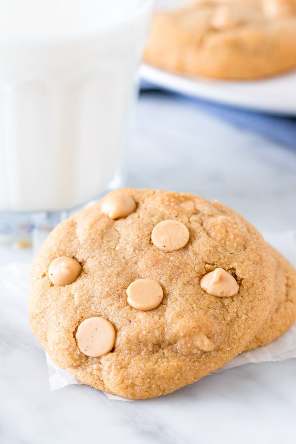 Peanut butter cookie with peanut butter chips and a glass of milk.