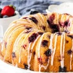 A berry bundt cake on a plate with a drizzle of glaze on top
