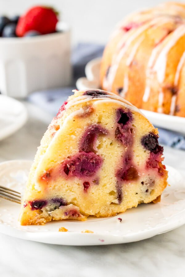 Slice of berry pound cake on a plate.