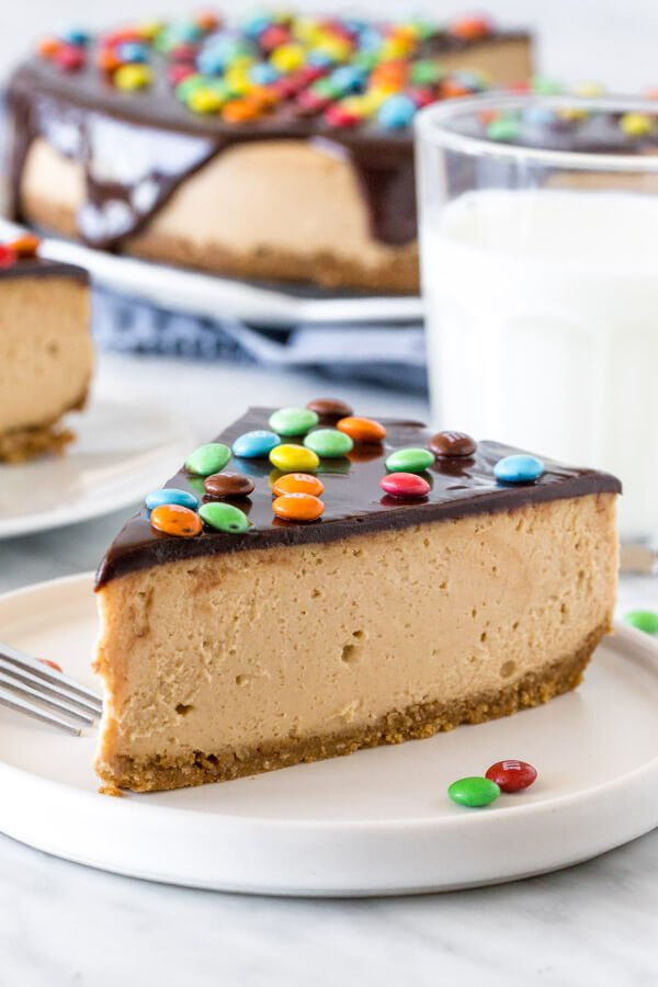 Slice of monster cookie cheesecake with a glass of milk. 2nd piece of cheesecake and entire cheesecake in the background.