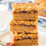 Stack of 3 peanut butter and jelly bars with a glass of milk.