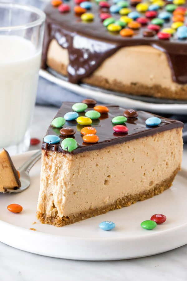 Slice of monster cookie cheesecake with a bite taken out of it.