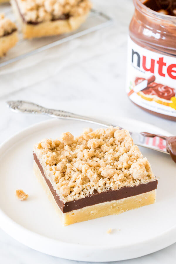 Nutella shortbread bar on a plate with a jar of Nutella