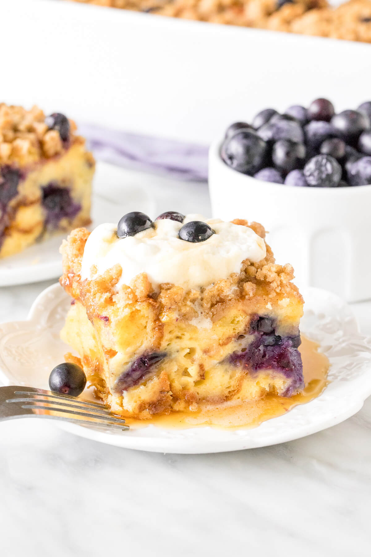 Slice of blueberry french toast casserole with whipped cream on top.