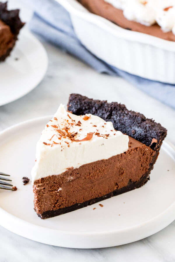 Slice of chocolate mousse pie with whipped cream on a white plate.
