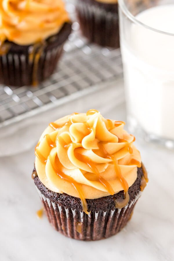Cupcake topped with caramel buttercream and drizzled with salted caramel drizzled on top with a glass of milk.