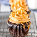 Chocolate cupcakes with caramel frosting and caramel sauce.