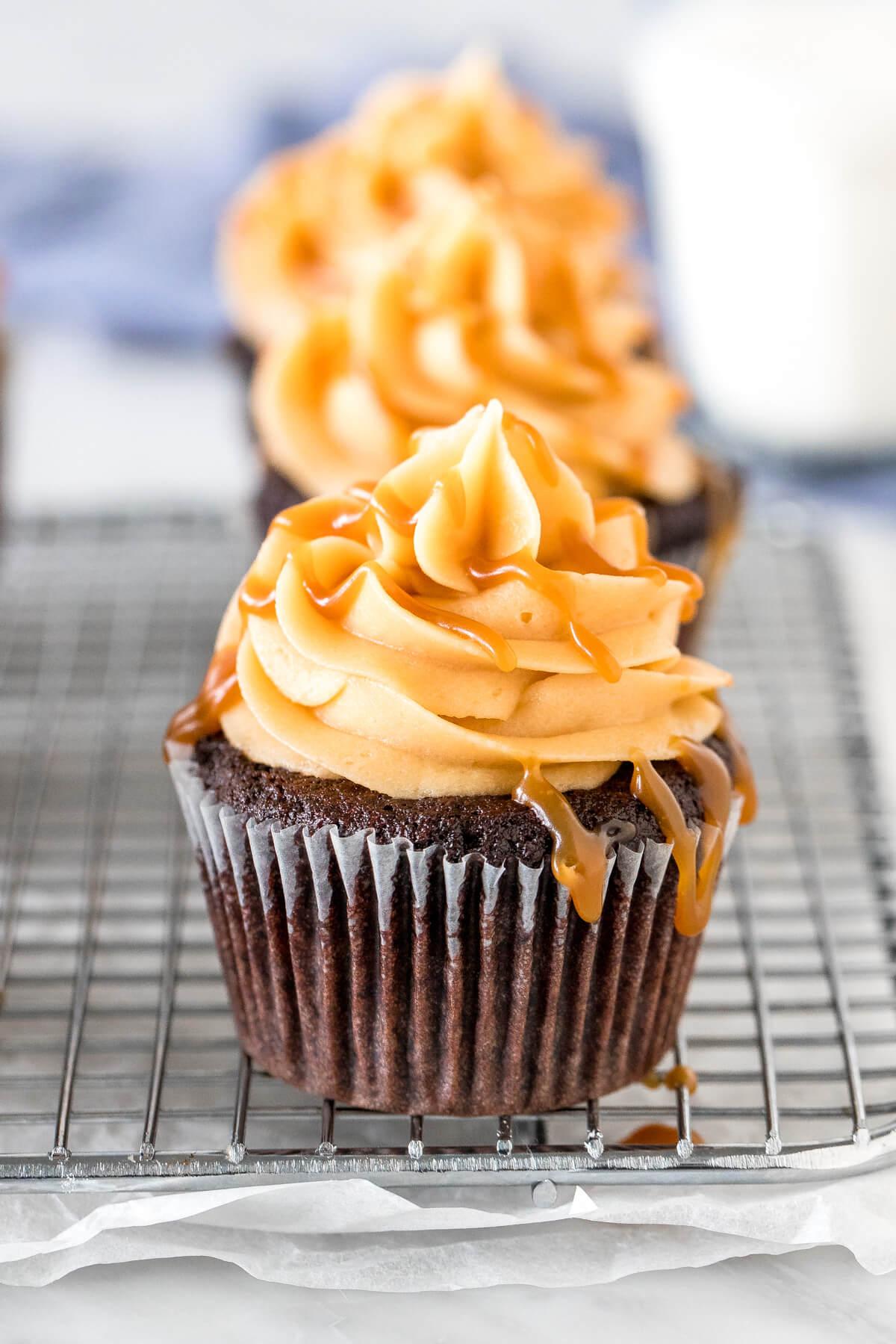 Chocolate cupcakes with caramel frosting and caramel sauce.