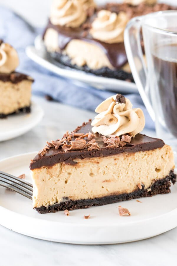 Slice of coffee cheesecake with chocolate ganache on top on a plate.