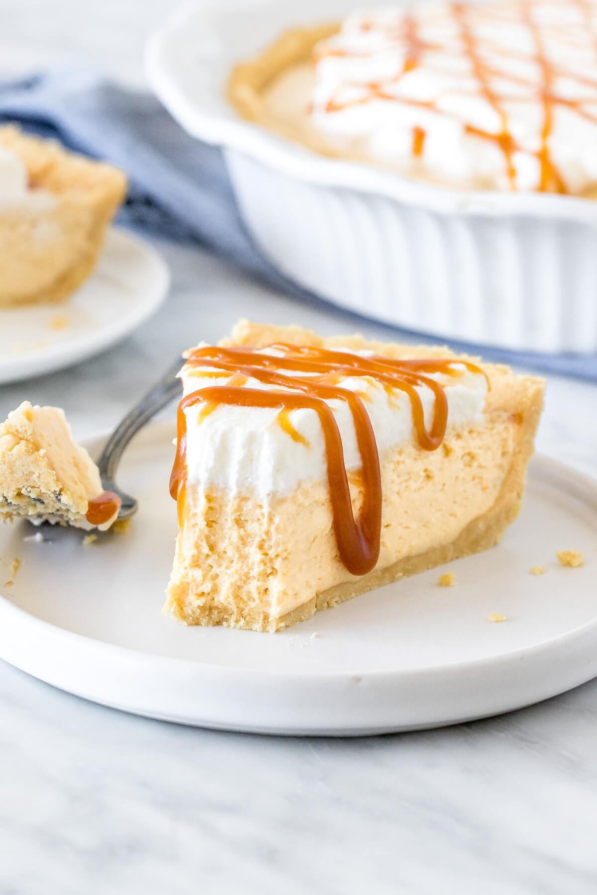 Slice of no-bake caramel cream pie with a bite taken out of it.