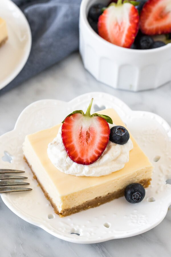 Cheesecake square on a plate, topped with cream and berries.