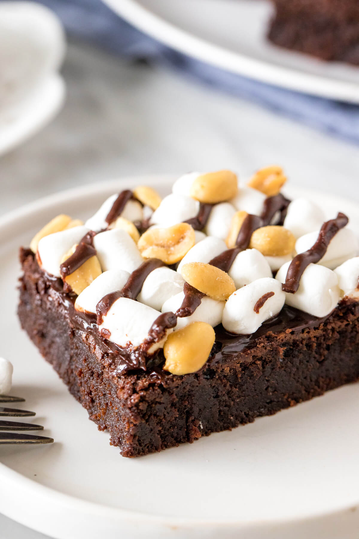 Piece of rocky road brownie topped with marshmallows and peanuts