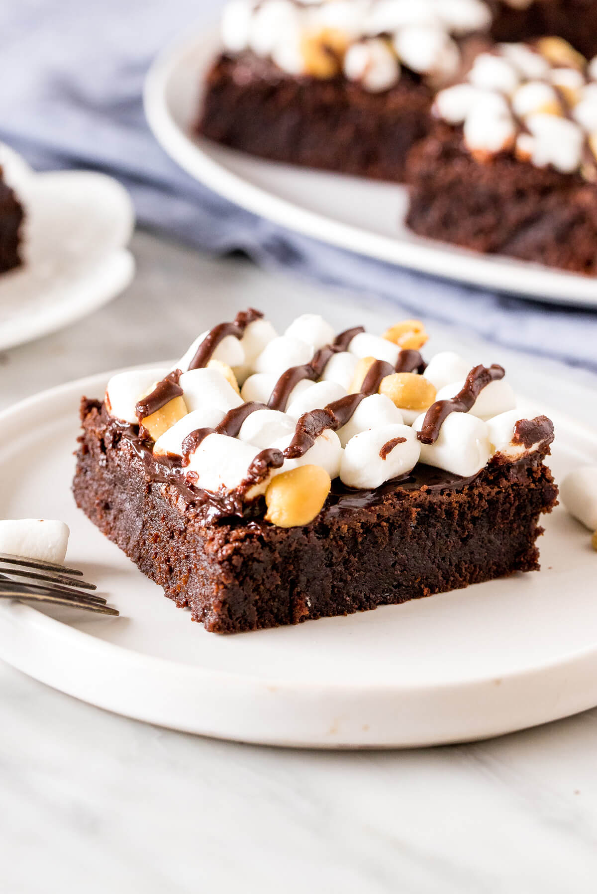 A rocky road brownie with marshmallows and peanuts on a plate.