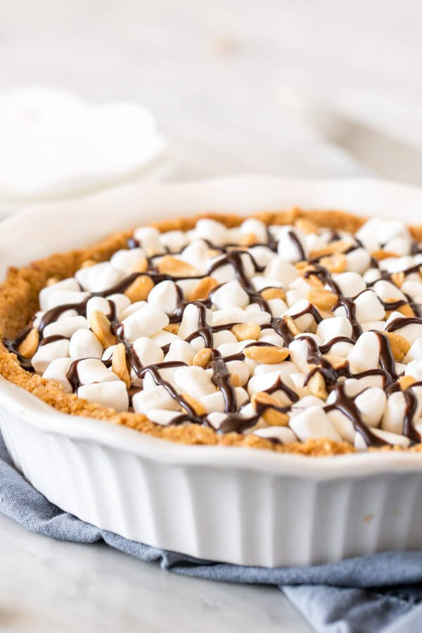 Rocky road cheesecake in a pie pan topped with marshmallows, peanuts and chocolate.