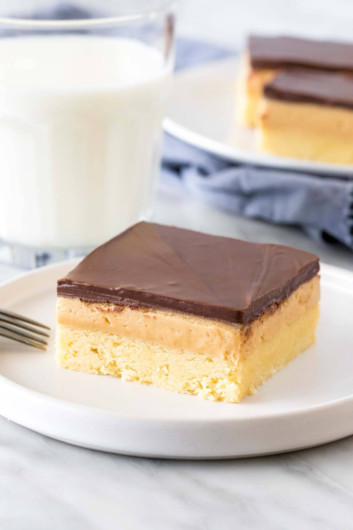 Peanut butter millionaire's shortbread bar on a plate with a glass of milk.