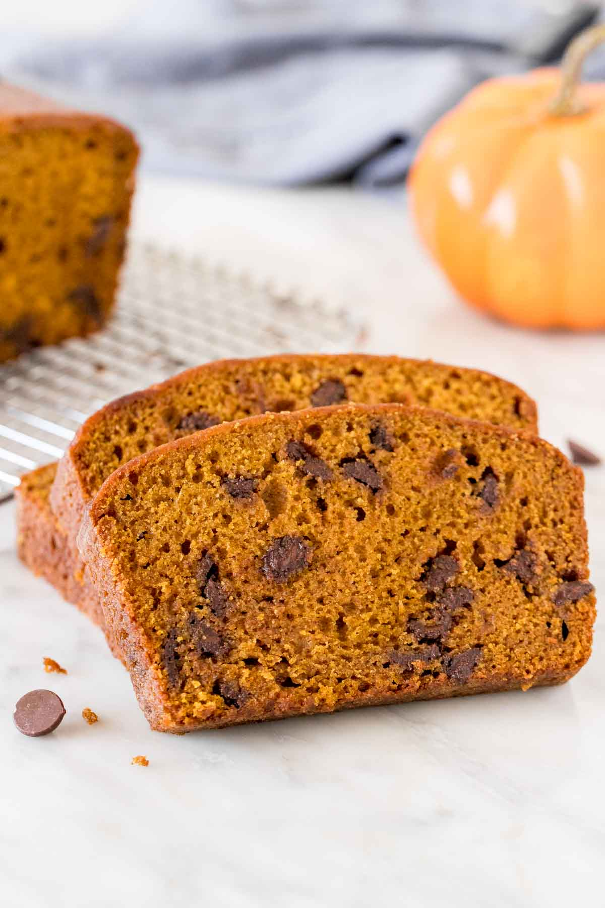 Slices of pumpkin chocolate chip bread beside half a loaf on a cooling rack.